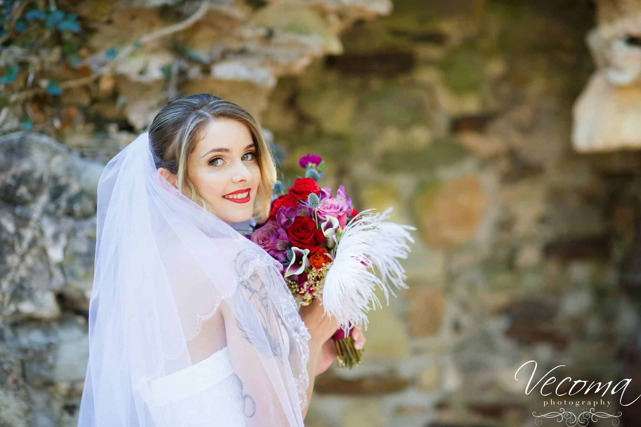 Beautiful bride with stunning bouquet of lilies roses and feathers