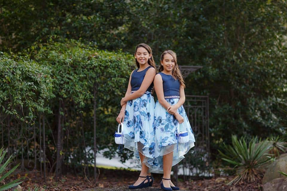 Flower girls in blue floral dresses outdoors at a wedding reception in