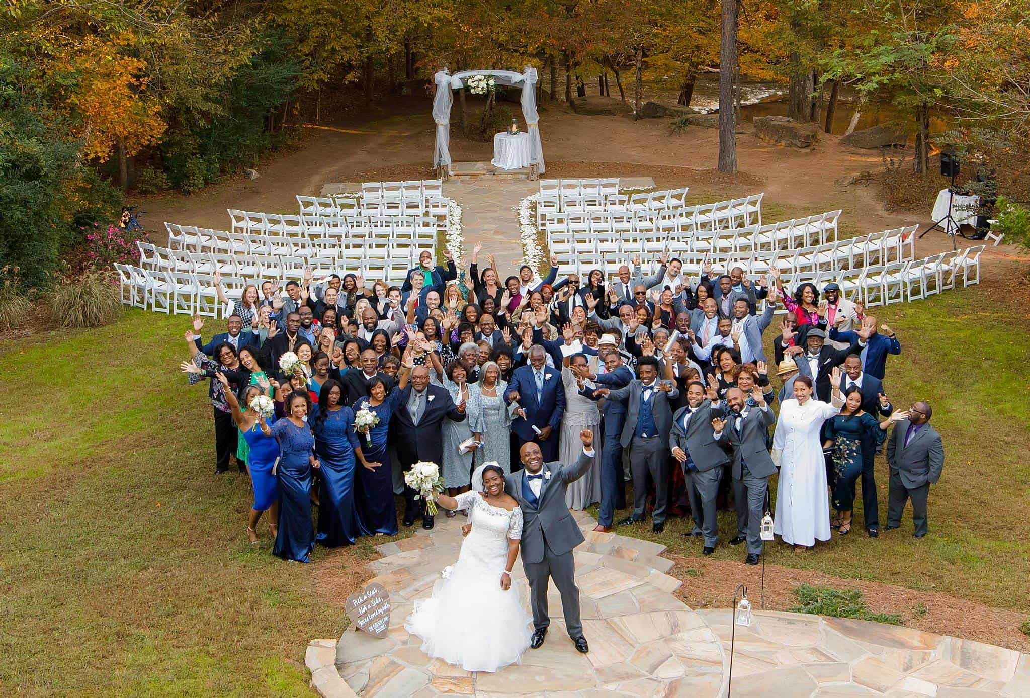 Aerial view of entire wedding party and guests cheering on bride and groom
