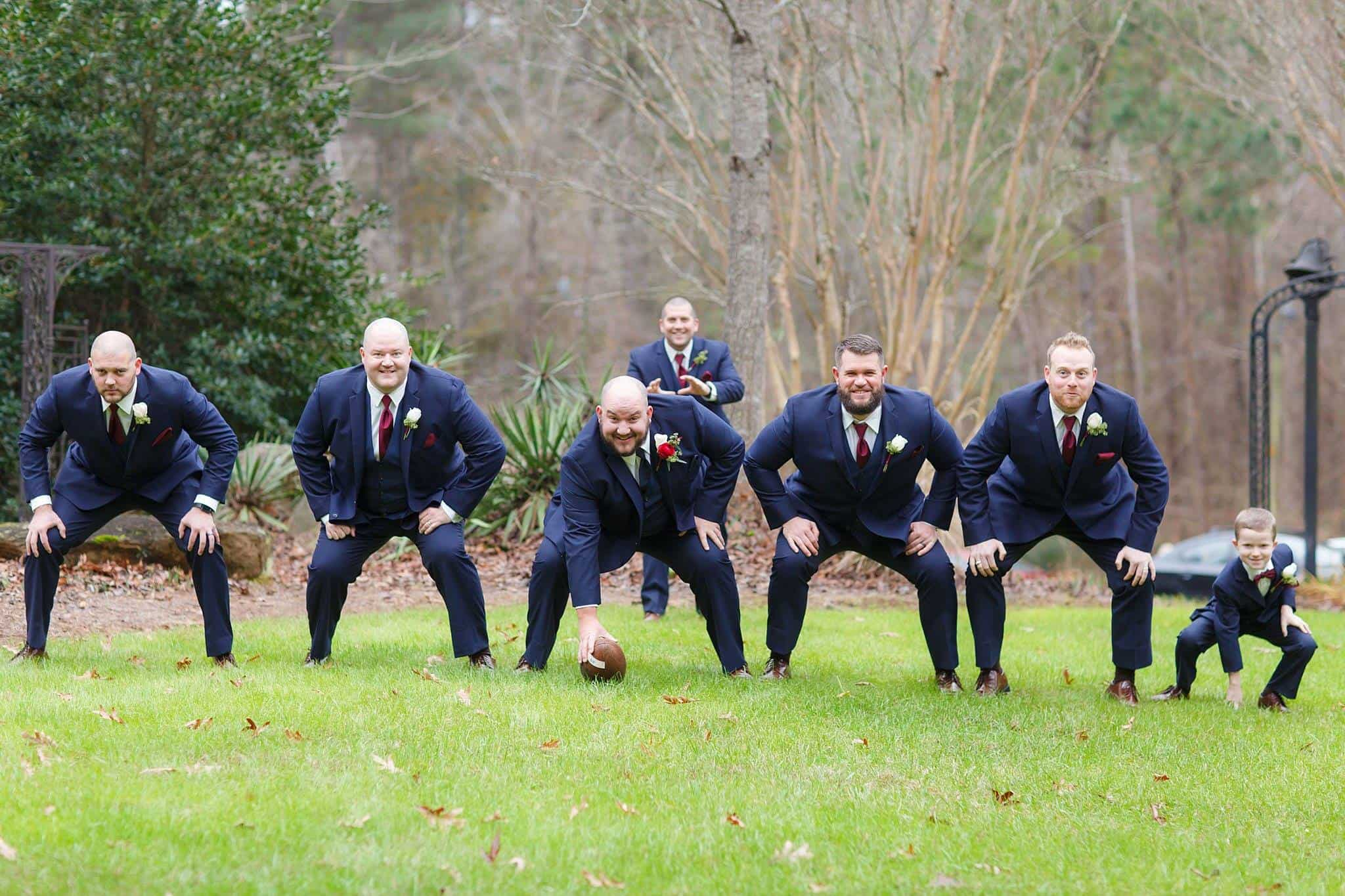 Groom with groomsmen posing with a football outdoors on the front lawn of a wedding venue located close to Tucker