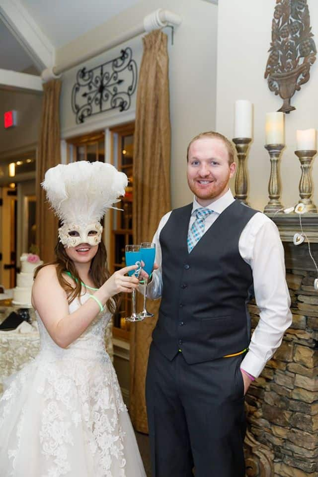 Bride with White Feathered Mask toasting signature blue cocktail with groom