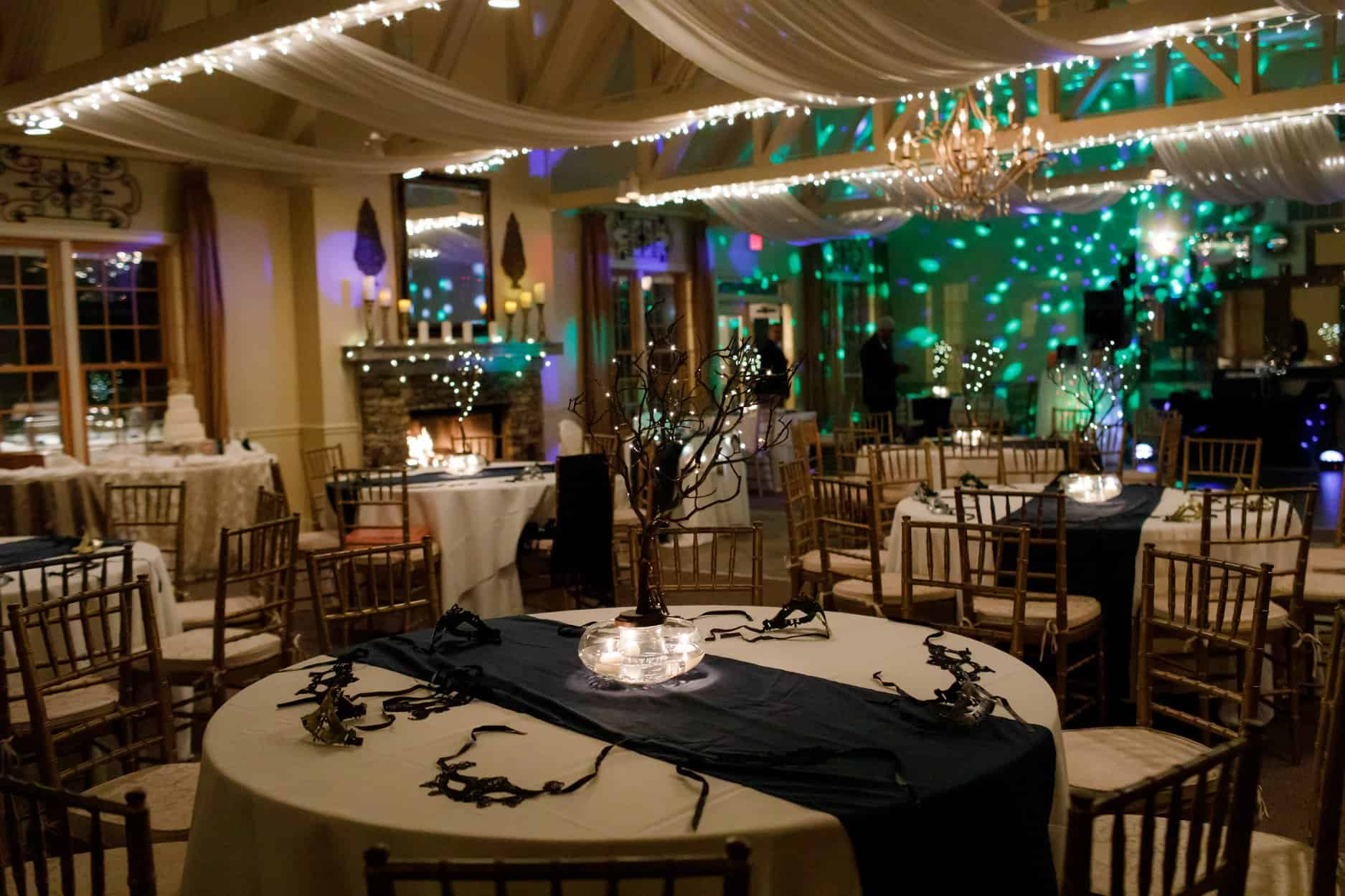 Guest tables at wedding reception with black runners, tall centerpieces and black masks