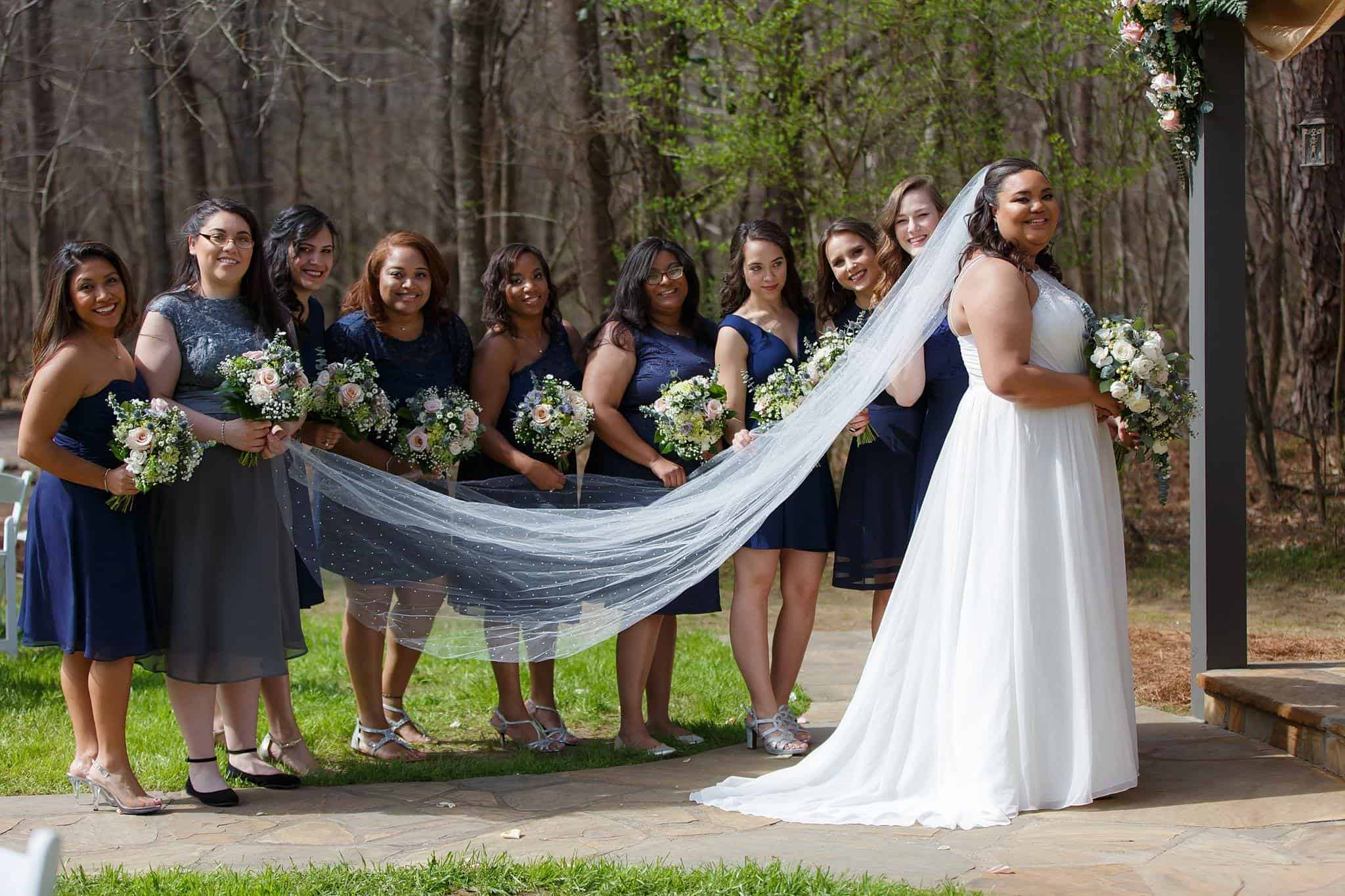 Bride with Bridesmaids in Blue Bridesmaids Dresses holding Cathedral Length Veil with Polka Dots