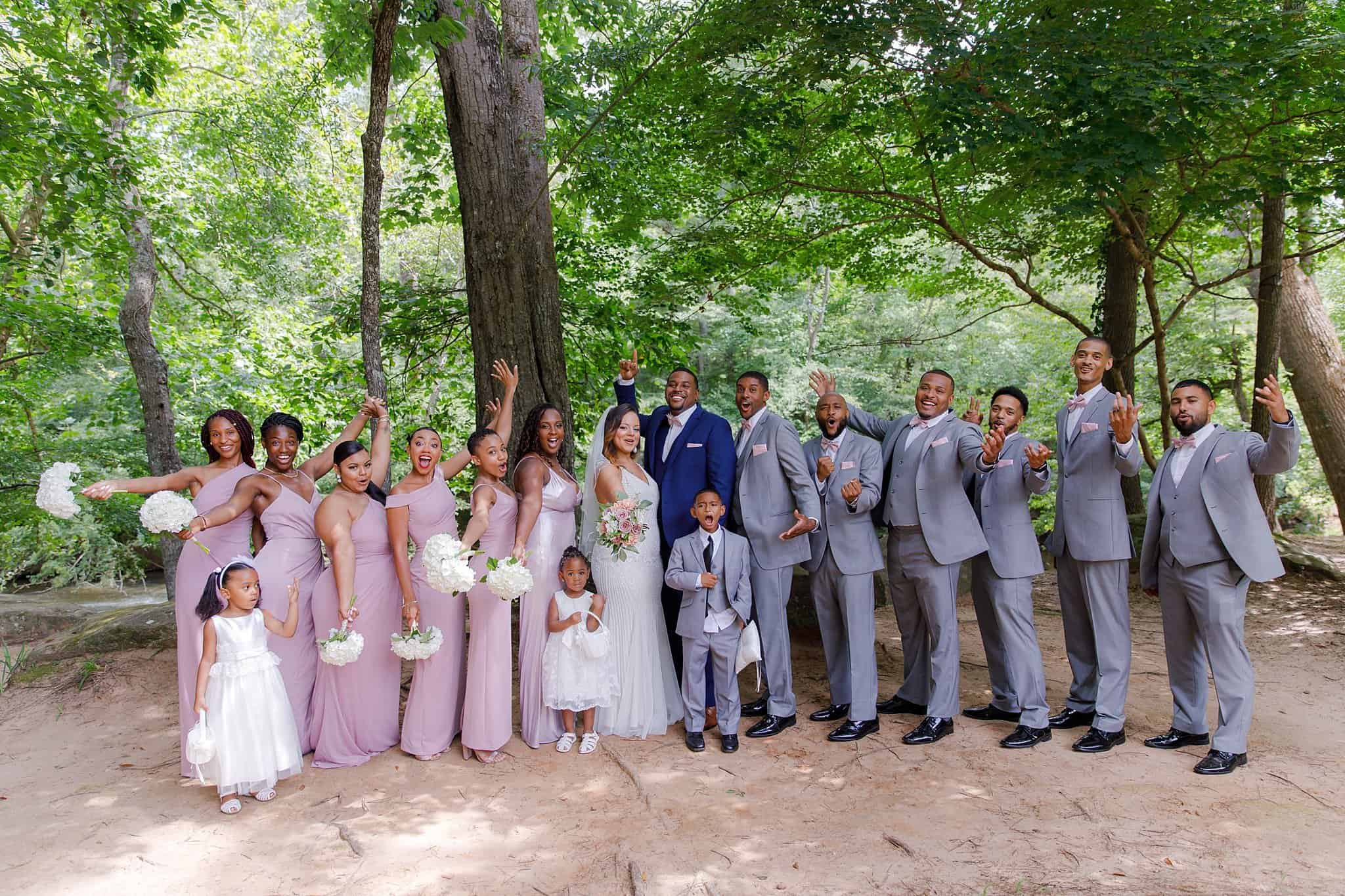 Bridesmaids in lilac bridesmaids dresses holding white hydrangea flowers with groomsmen wearing soft gray suits with lilac bow ties posing outdoors with bride and groom outdoors with flowergirls and ringbearer
