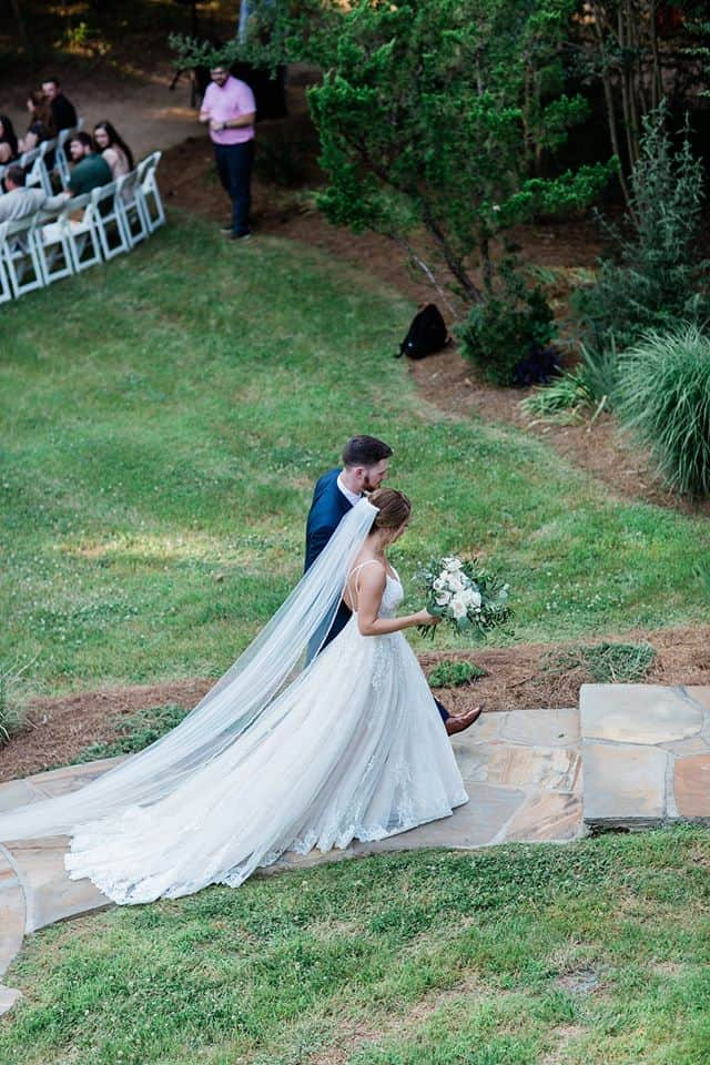 Bride and Groom walking up steps during recessional holding hands