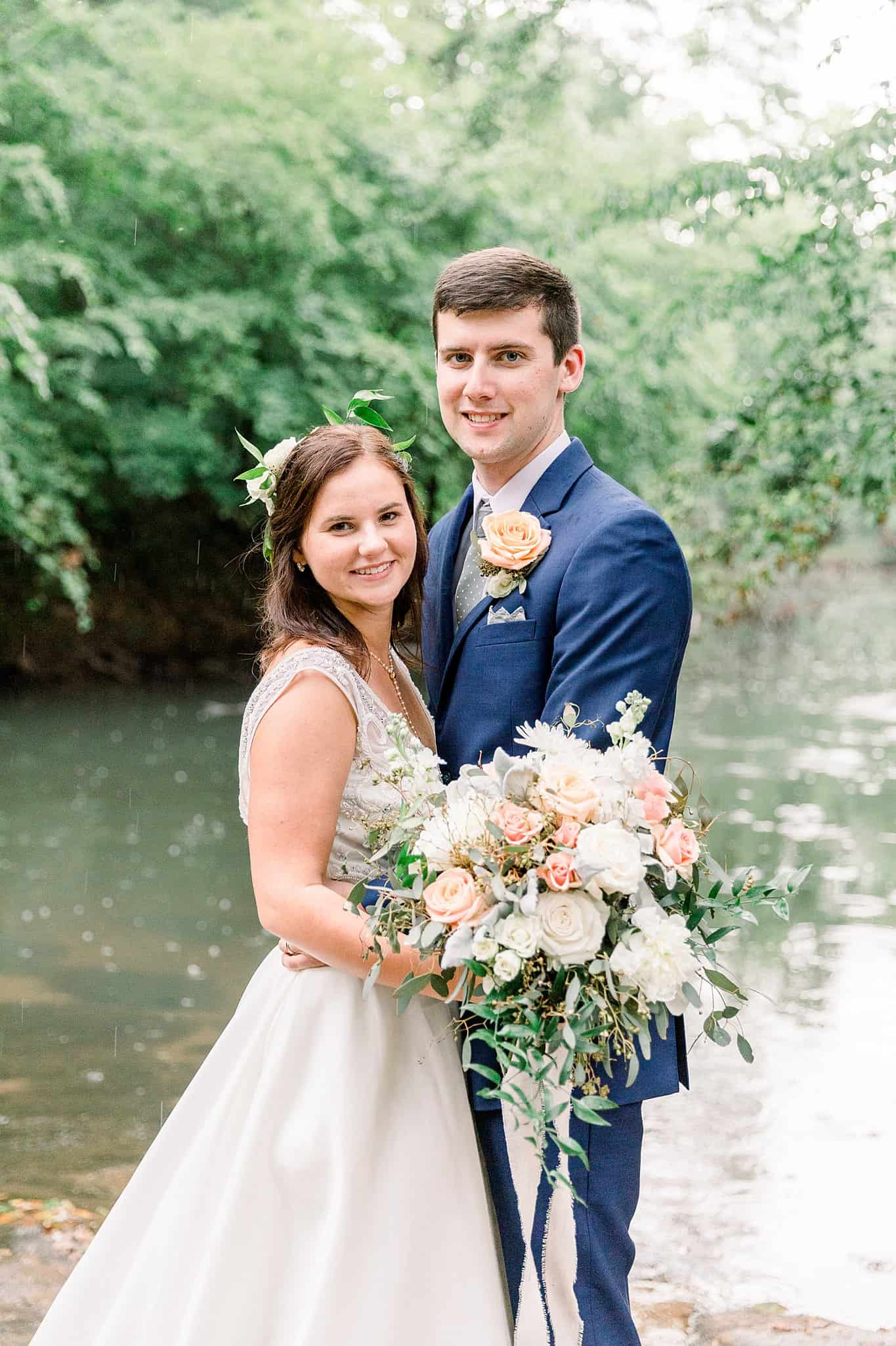 bride and groom pose on the riverbank