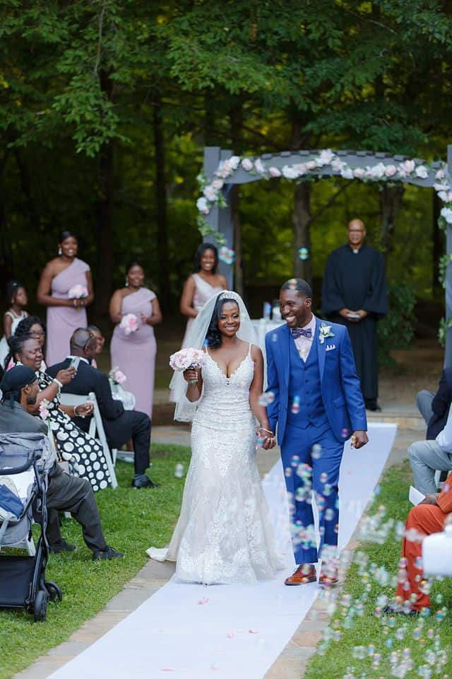 Bride and Groom at wedding ceremony recessional walking down white aisle runner with bubbles