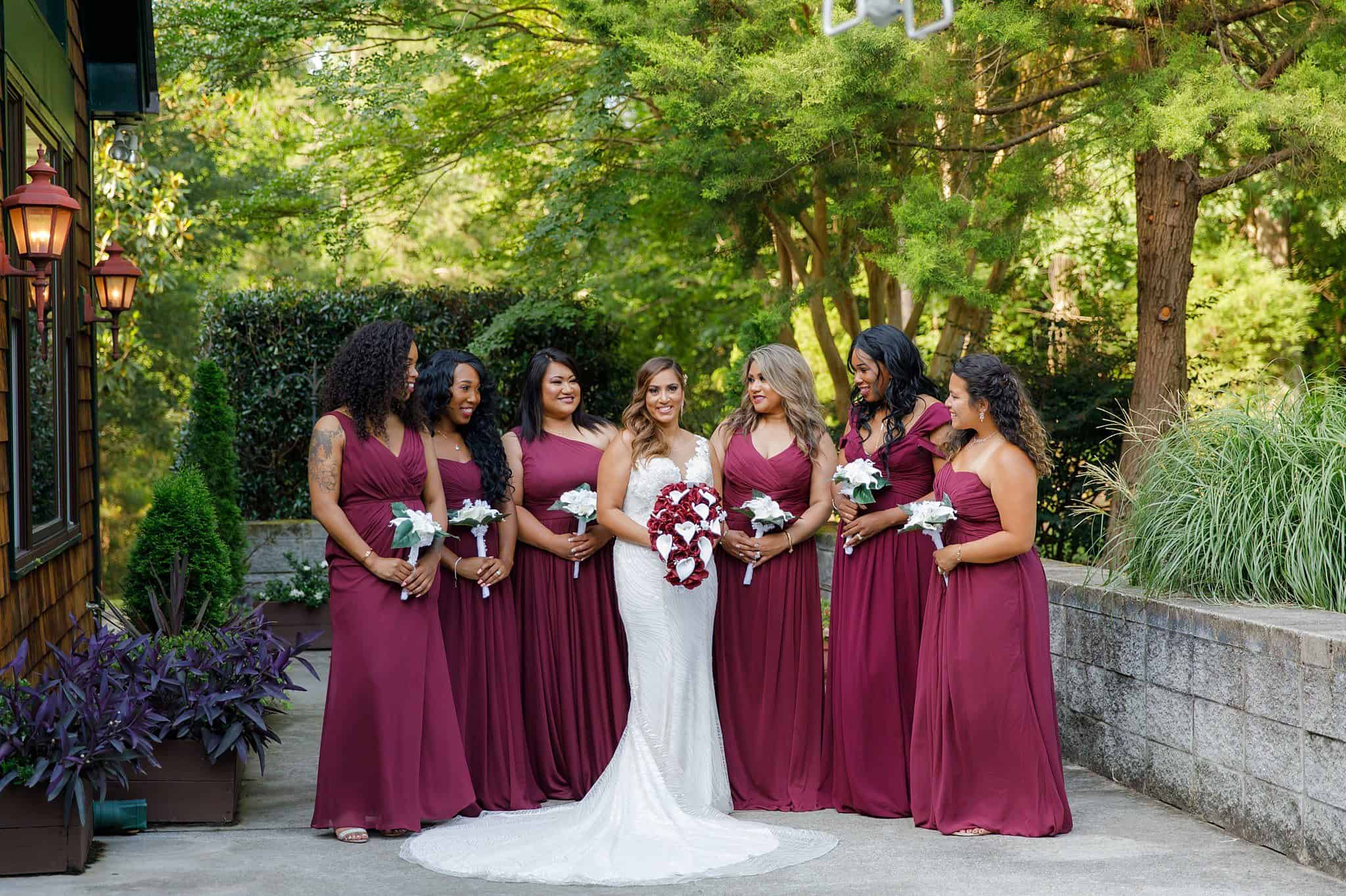 bride with bridesmaids in burgundy gowns