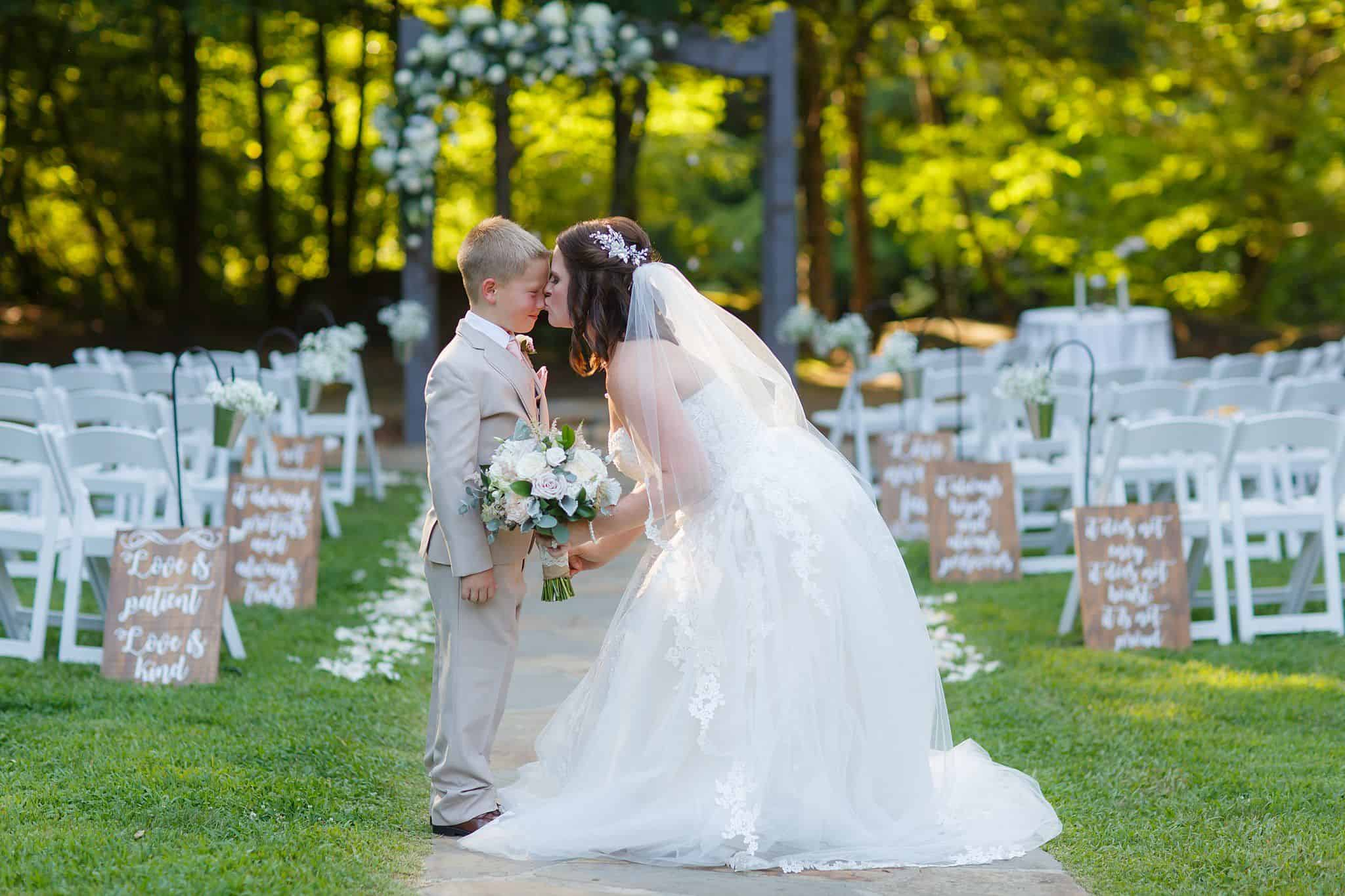 Bride kissing ringbearer on his nose holding her bouquet in front of the ceremony space for her wedding outdoors