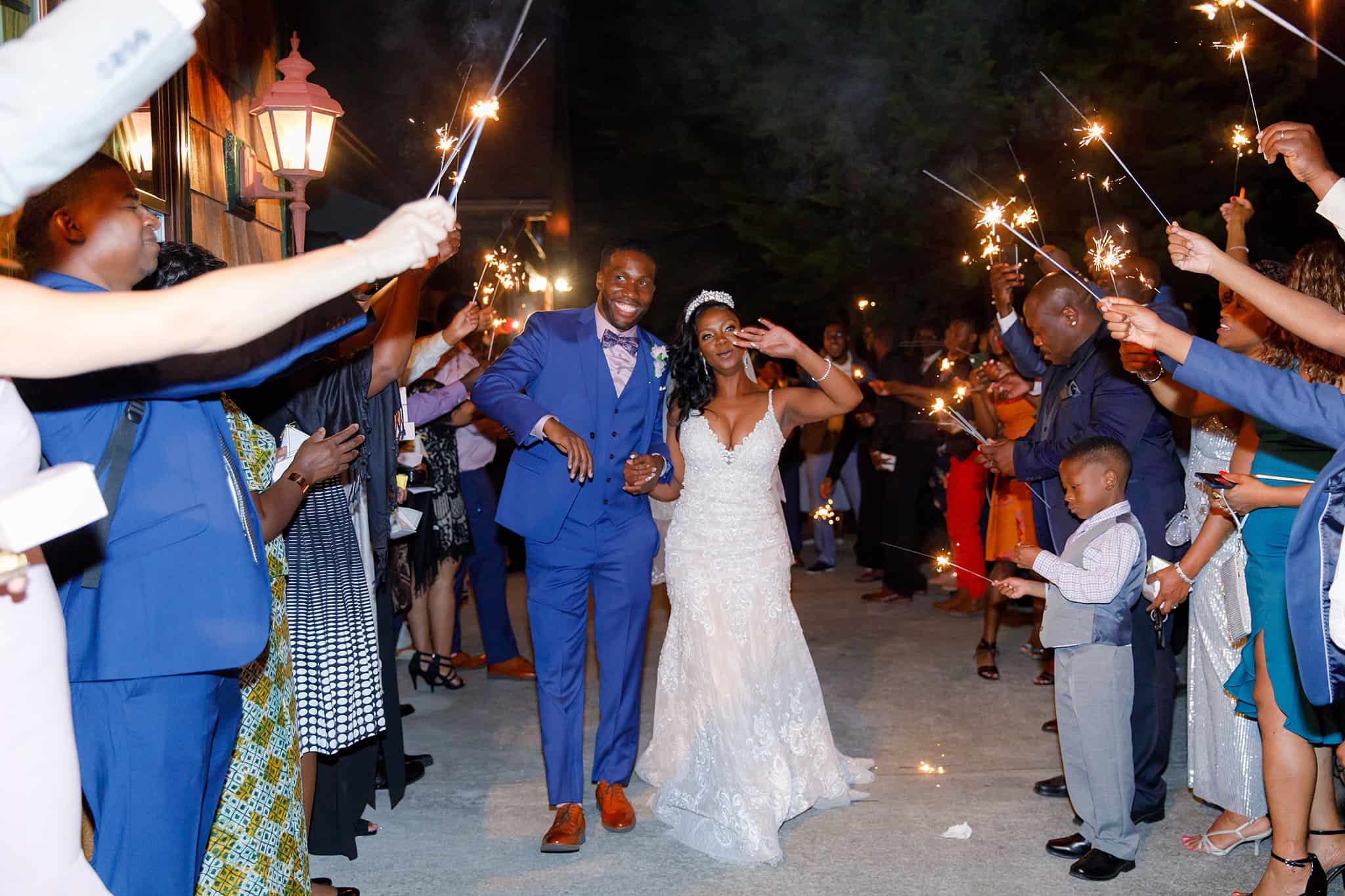Bride and Groom departing wedding reception as guests hold sparklers