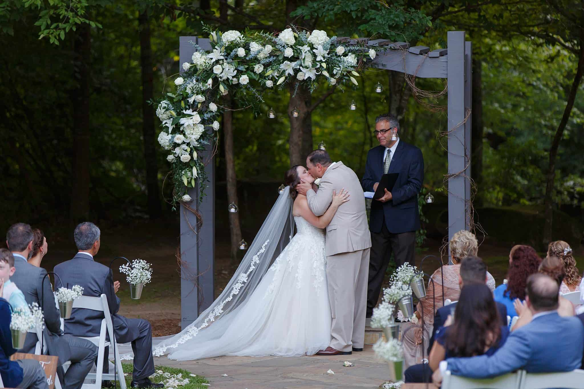 Bride and Groom Kissing at Altar during outdoor ceremony while being announced husband and wife