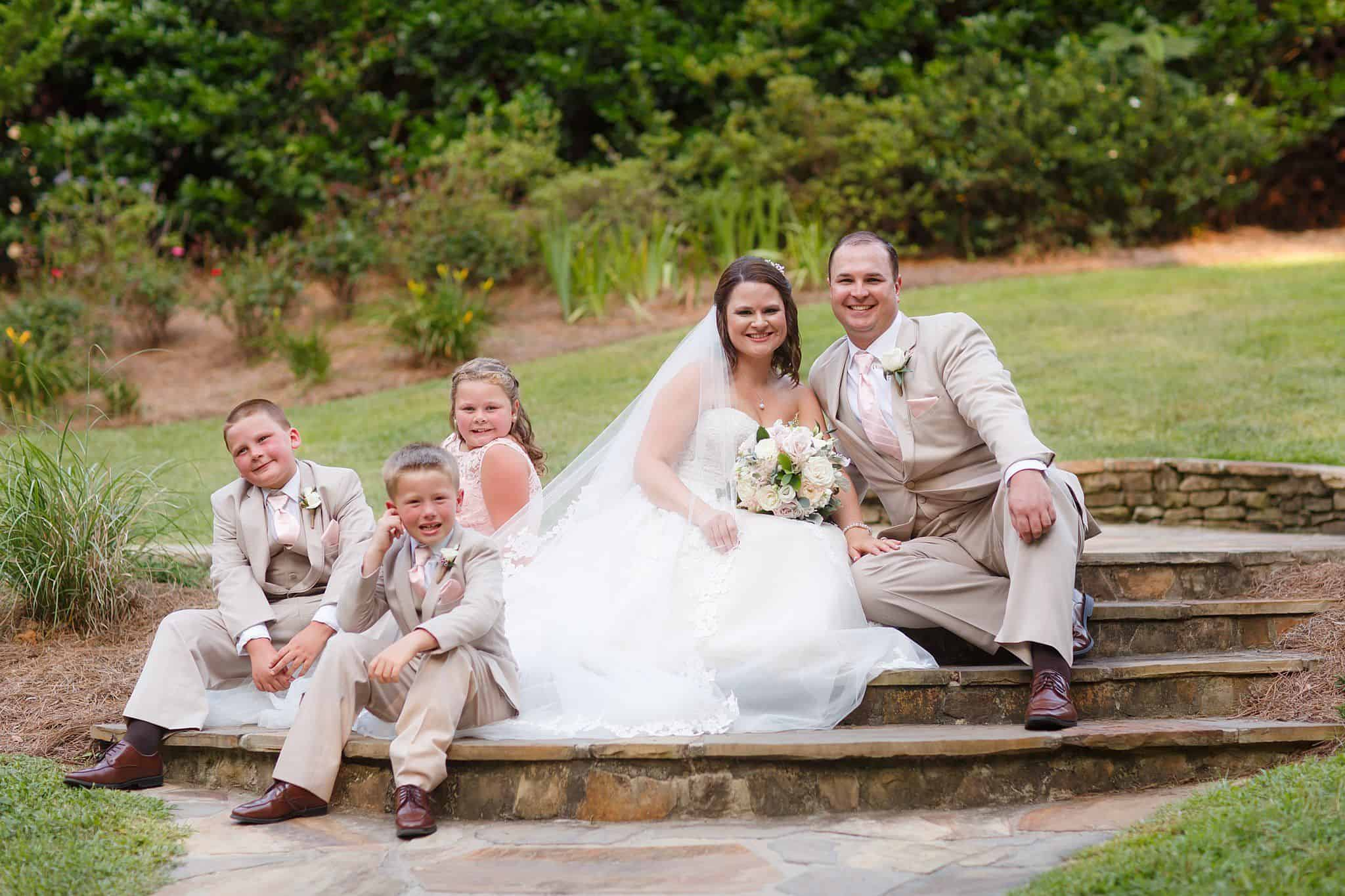 Bride and Groom sitting down with two boys and flowergirl on paved steps outdoors