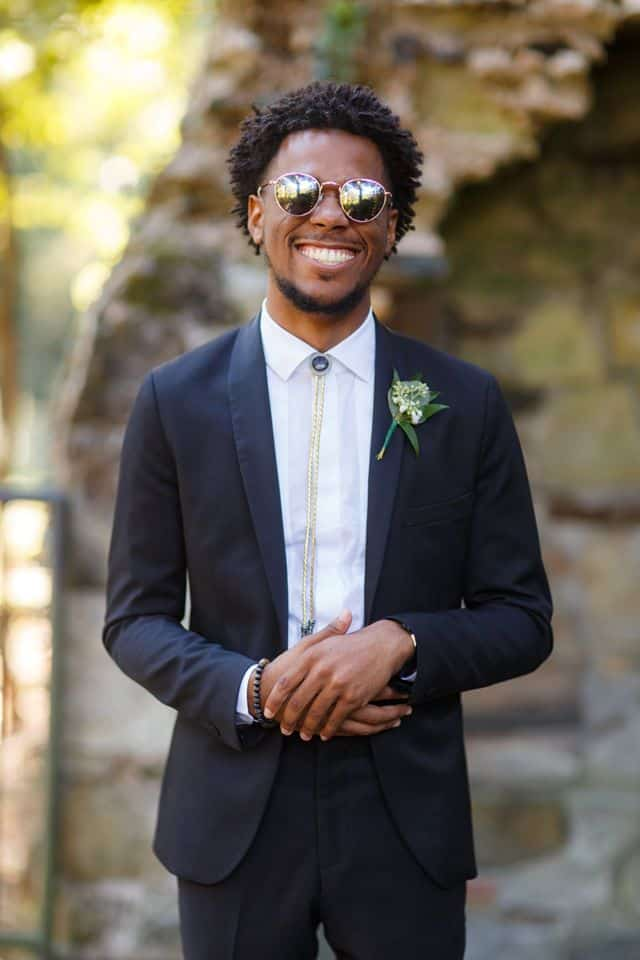 Smiling Groom in front of outside chimney in black suit and sunglasses