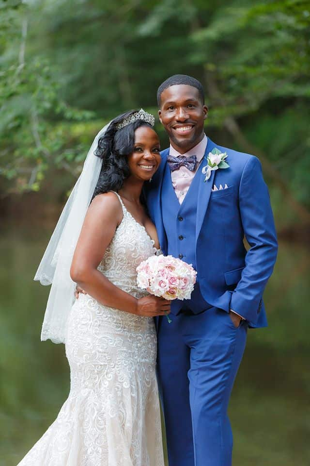 Bride and Groom posing on the river outdoors in bridal gown holding bridal bouquet