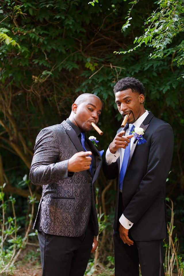Groom with Best Man posing with cigars and pointing at photographer outdoors