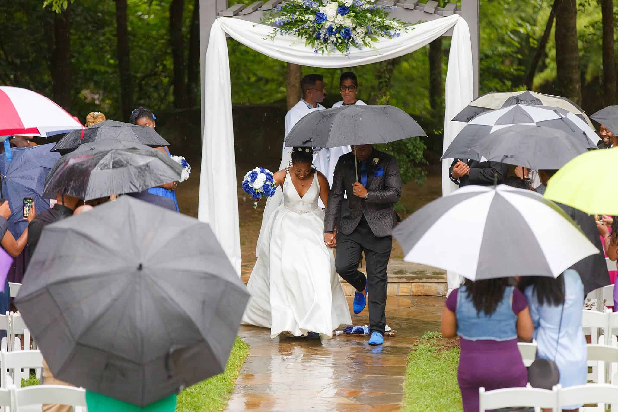 Bride and Groom leaving wedding altar in the rain after jumping the broom
