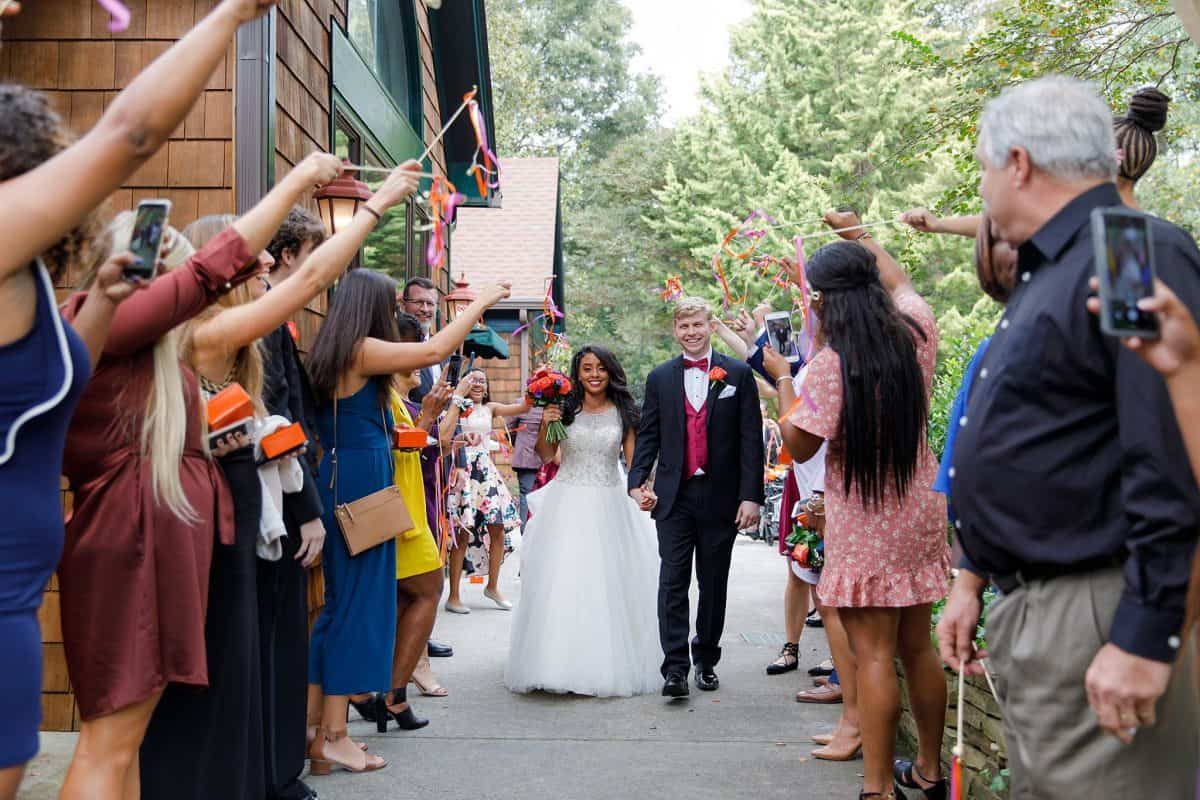 Bride and Groom walk through parage of colorful streamers