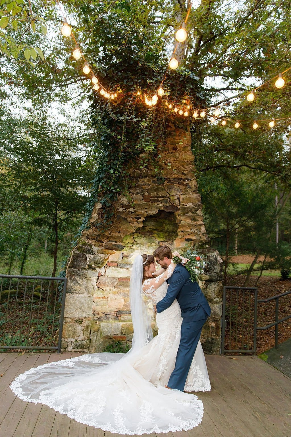 Bride and Groom by chimney ruins Bride in long sleeve gown Groom is dipping the Bride
